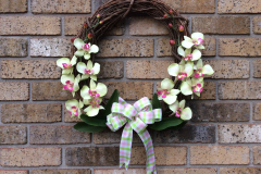 """17"""" Grapevine with Green + Pink Orchids and Pink/Green Checked Wired Ribbon."""