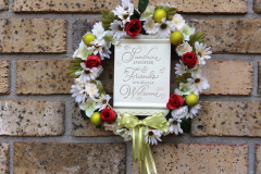 "12"" Grapevine with Ceramic Plaque ""Sunshine Laughter & Friends Are Always Welcome"", Daisies, Mini Roses and Green Balls."
