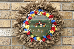 """17"""" Burlap with Hand-Painted Wood Centre (Village Scene), with Mini Red, White, Yellow, Blue Flowers."""