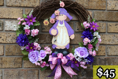 "17"" Grapevine with Hand-Painted Wooden Girl, Mauve Roses, Dark Purple Daisies and Mums. $45."